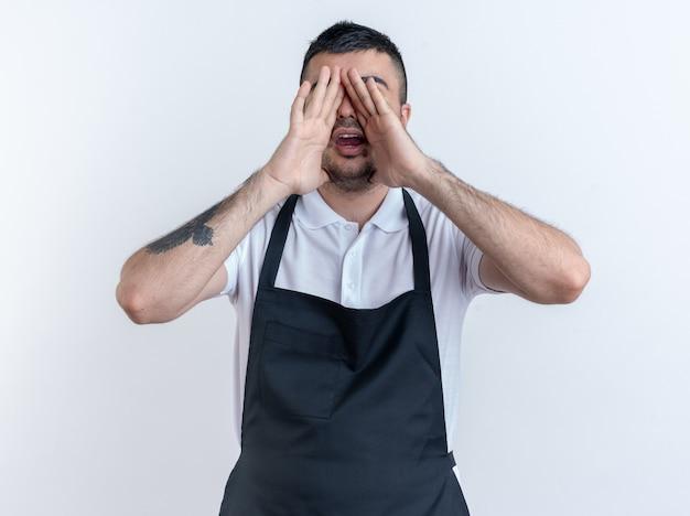 Friseur mann in schürze schreien mit den händen in der nähe des mundes stehend auf weißem hintergrund
