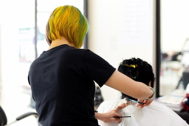 Friseur mit der bunten frisur der mode, die alte dame schneidet, ist haar