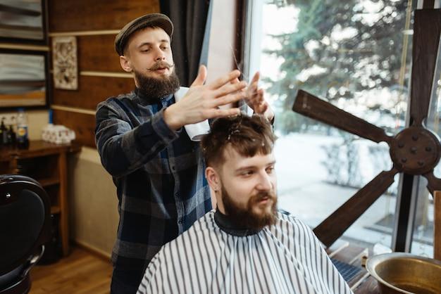 Friseur mit hut und bärtigem kunden. professioneller barbershop ist ein trendberuf