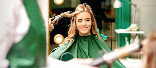 Friseur mit lockenstab lockt langes braunes haar auf dem jungen kaukasischen mädchen in einem schönheitssalon