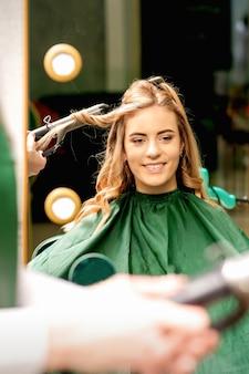 Friseur mit lockenstab lockt langes braunes haar auf dem jungen kaukasischen mädchen in einem schönheitssalon.