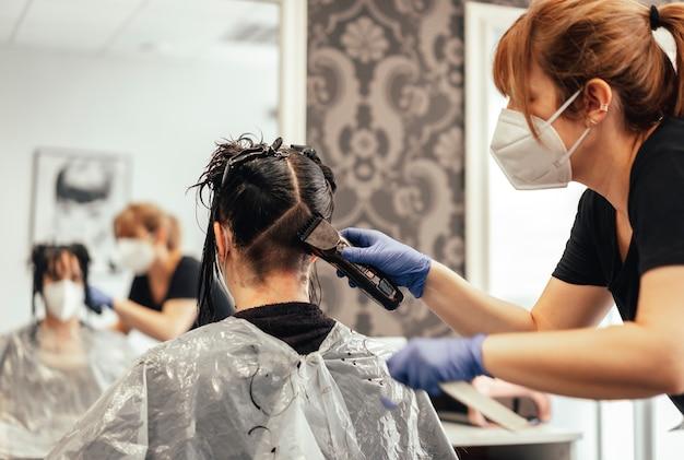 Friseur mit maske und handschuhen, die sich mit rasiermesser rasieren. wiedereröffnung mit sicherheitsmaßnahmen von friseuren in der covid-19-pandemie