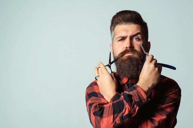 Friseur mit rasiermesser und schere über blauer wand. brutaler mann, der professionelle werkzeuge hält. friseursalon.