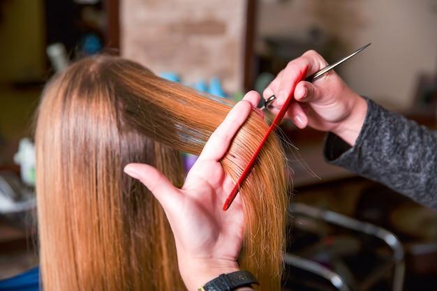 Friseur mit schere und kämmen süßem haar für junge frau.
