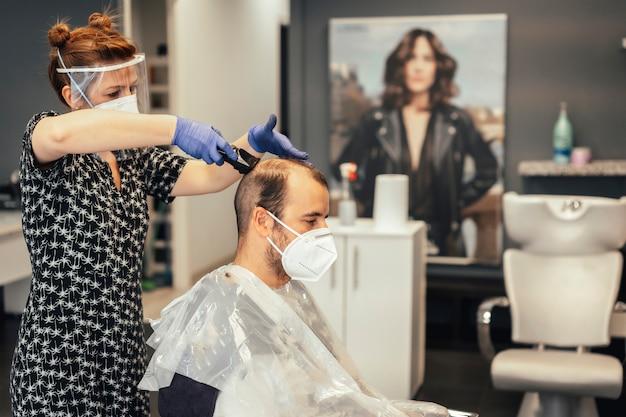 Friseur mit sicherheitsmaßnahmen der covid-19, neue normalität, soziale distanz, porträts von friseur und klient mit maske
