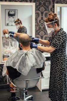 Friseur mit sicherheitsmaßnahmen für den covid-19, neue normalität, soziale distanz, friseur und kunde mit maske. maschinenschneiden von haaren