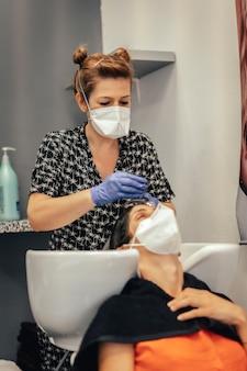 Friseur mit sicherheitsmaßnahmen für die covid-19, neue normalität, soziale distanz. friseur, der einem kunden mit maske haare mit wasser wäscht