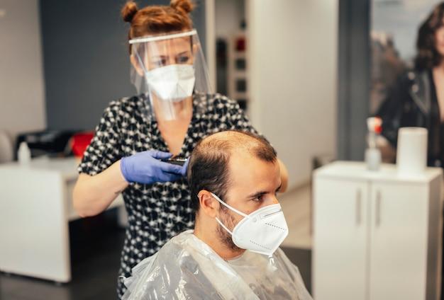 Friseur mit sicherheitsmaßnahmen für die covid-19, neue normalität, soziale distanz, haare schneiden mit einer maske