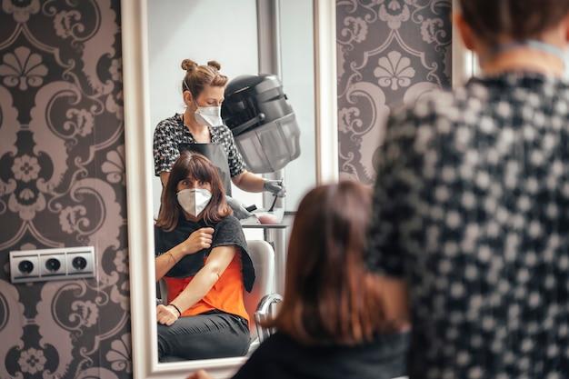 Friseur mit sicherheitsmaßnahmen für die covid-19, neue normalität, soziale distanz. pelura und klient mit maske im spiegel