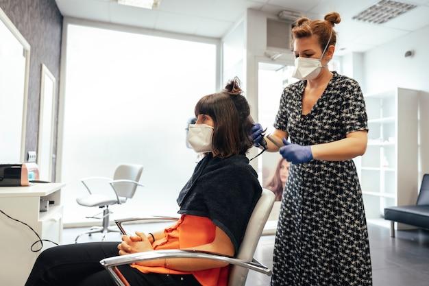 Friseur mit sicherheitsmaßnahmen für die covid-19, neue normalität, soziale distanz. schneiden der enden eines brünetten klienten