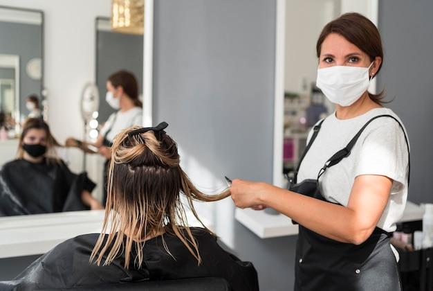 Friseur mit stoffmaske und kunde