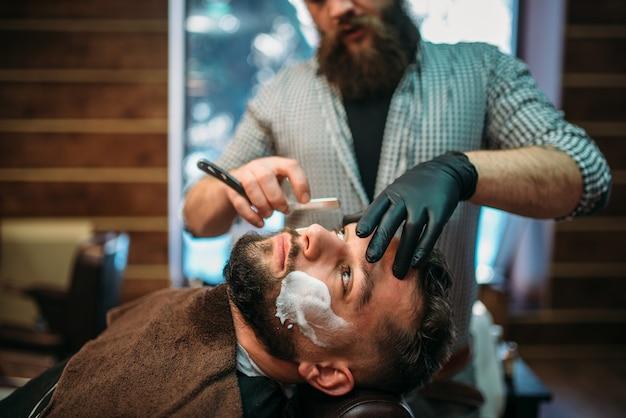 Friseur rasiert bart des kunden im friseursalon