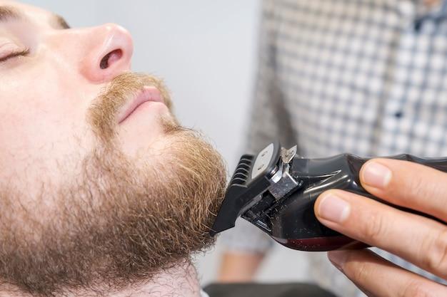 Friseur rasiert den bart seines kunden mit einem elektrischen trimmer.