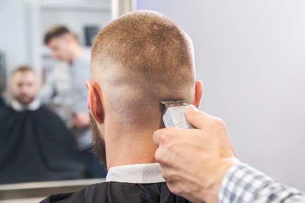 Friseur rasiert den kopf des kunden mit einem roten elektrischen trimmer.