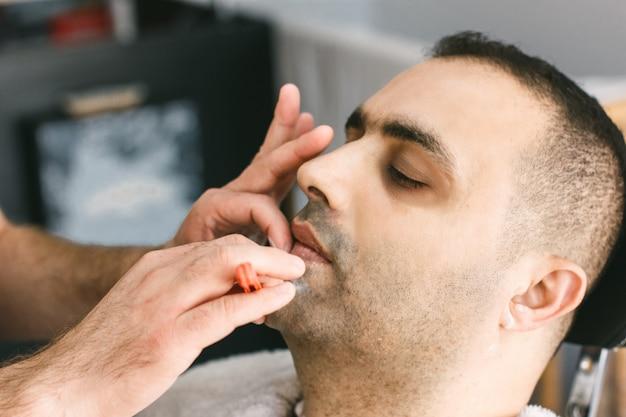 Friseur rasiert einem mann mit einem rasiermesser im friseursalon einen bart