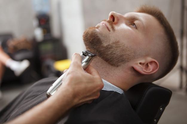 Friseur rasiert einen kunden im salon