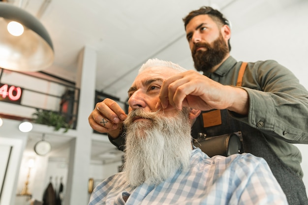 Friseur richten schnurrbart des älteren kunden gerade