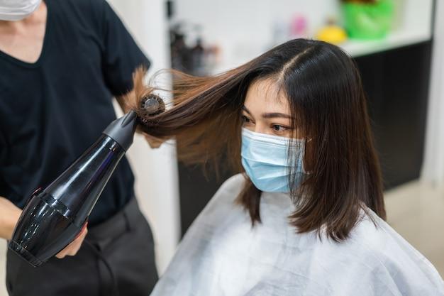 Friseur schneidet das haar zu kundin, die medizinische maske trägt, um coronavirus zu schützen
