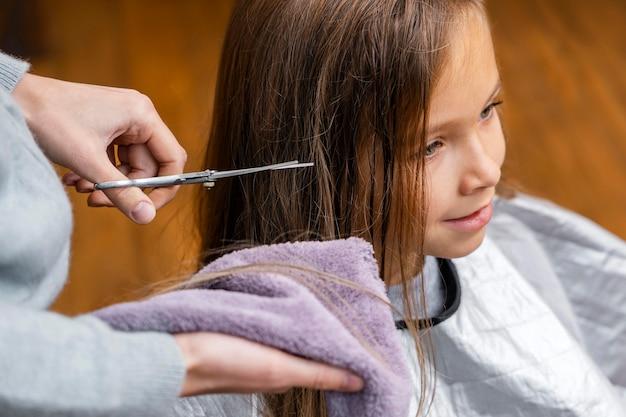 Friseur schneidet die haare des kleinen mädchens