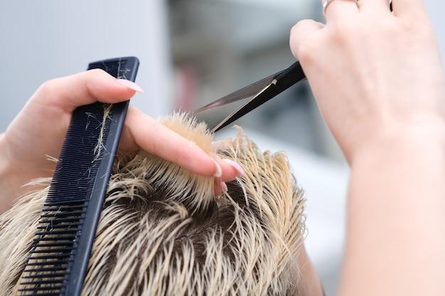Friseur schneidet einem jungen mann mit blond gefärbten haaren mit einer schere in einem schönheitssalon die haare. professionelle haarpflege.
