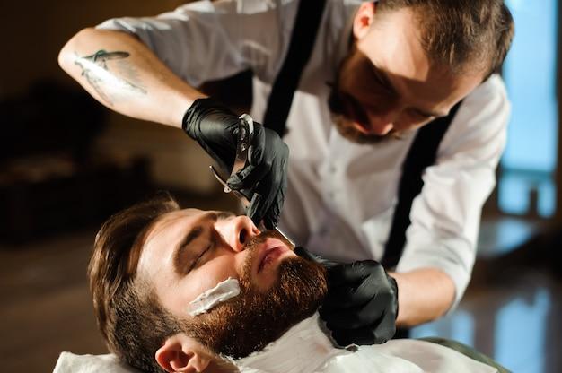 Friseur schneidet haare und bart eines mannes im friseursalon