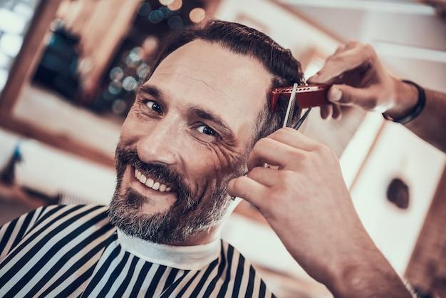 Friseur schneidet hübsche mann-seiten mit haarschneidemaschinen ab.