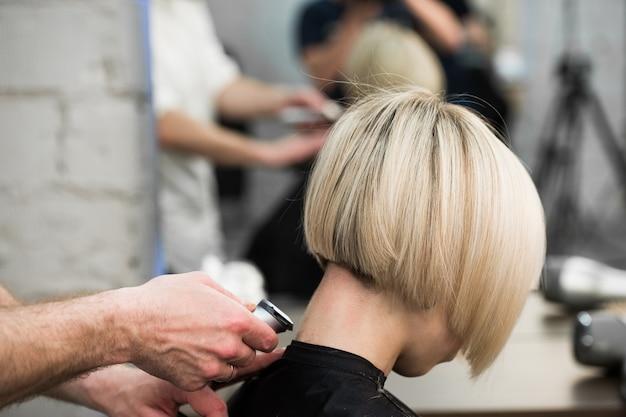 Friseur schneidet kundenhaar im salon mit elektrorasierer nahaufnahme.
