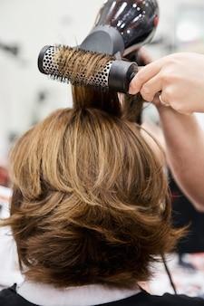 Friseur schneidet und kämmt haare mit föhn zur blonden dame