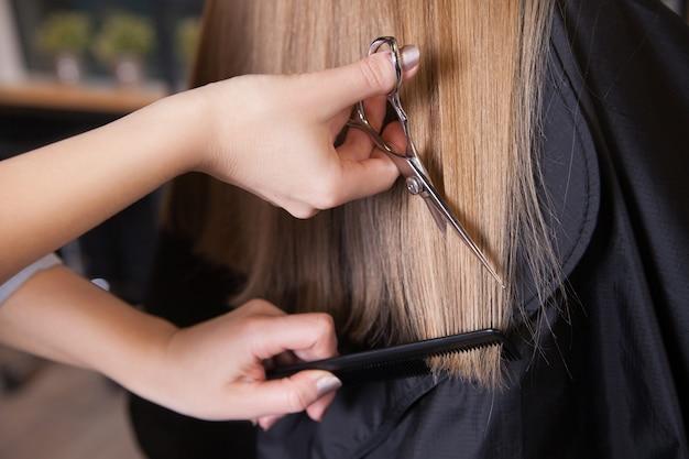 Friseur schnitt blondes haar einer frau. nahaufnahme.