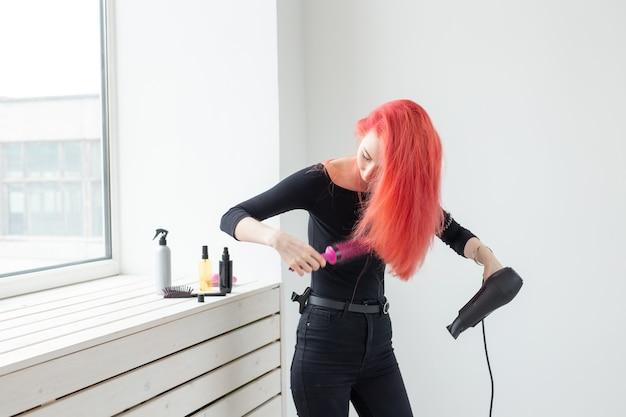 Friseur, schönheitssalon und leutekonzept - friseur der jungen frau mit haartrockner auf weißem hintergrund.