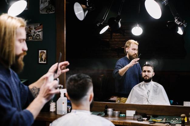 Friseur spritzt wasser auf die haare