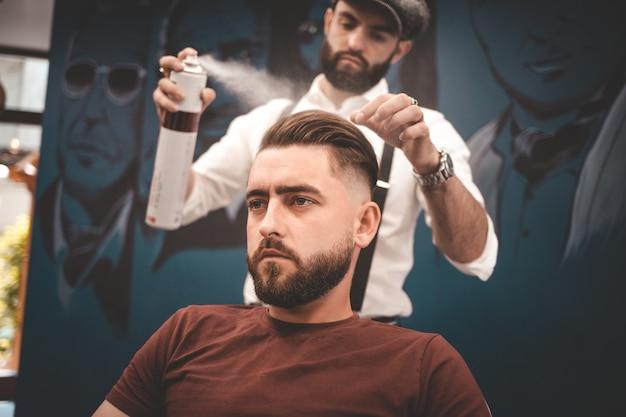 Friseur sprüht lack auf die haare des kunden