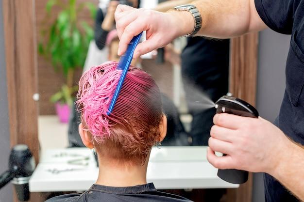 Friseur streut wasser auf die haare.