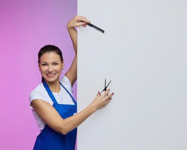 Friseur stylist von asiatischem aussehen posiert mit einer weißen plakatwand. werbekonzept