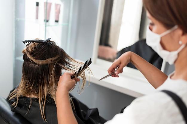 Friseur trägt stoffmaske hohe ansicht