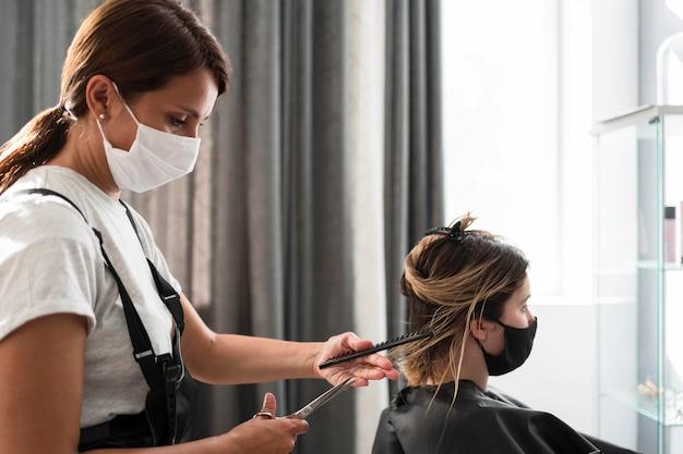 Friseur trägt stoffmaske seitenansicht