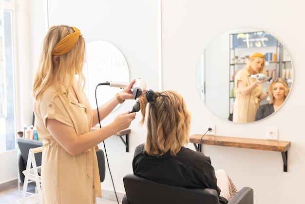 Friseur trocknet die haare einer blonden frau in ihrem friseursalon blick von hinten