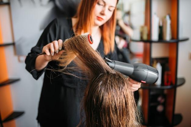 Friseur trocknet haare mit einem trockner, weibliche frisur im friseursalon. frisur machen im schönheitssalon
