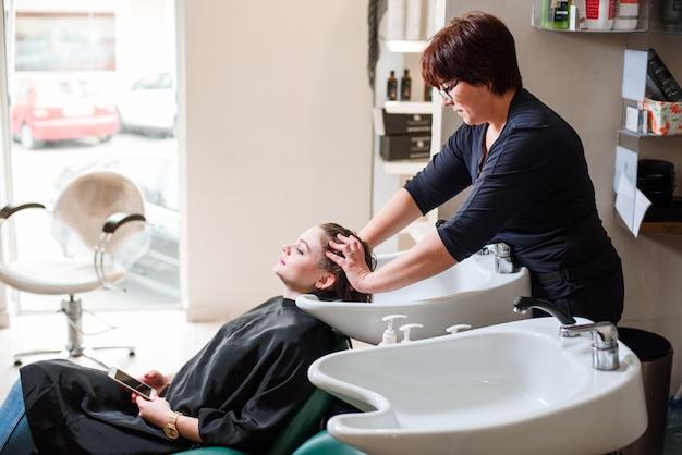 Friseur und frau während der haarwäsche