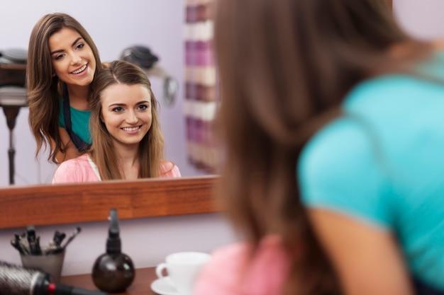 Friseur und kunde sprechen im friseursalon