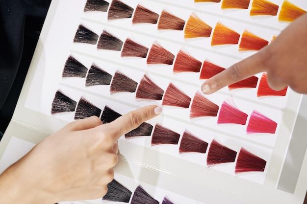Friseur und kunde untersuchen die haarfarbe