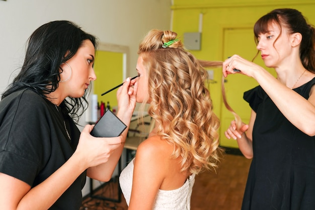 Friseur und visagistin, die im schönheitssalon mit model arbeiten
