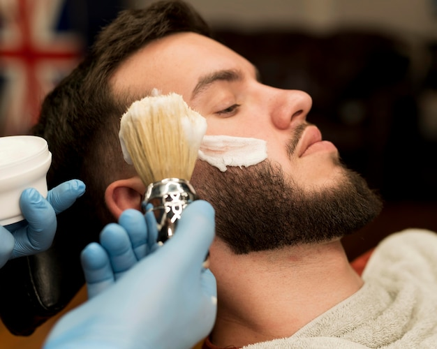 Friseur verwendet rasierschaum, um den bart eines männlichen kunden zu konturieren