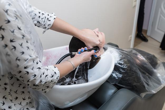 Friseur wäscht einem mädchen beim friseur die haare