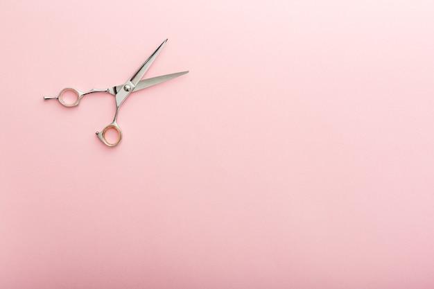 Friseur werkzeuge. friseurschere auf rosafarbenem hintergrund mit kopienraum für text. friseurservice. schönheitssalon-service.