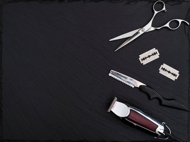 Friseurausrüstung auf schwarzem hintergrund mit platz für text. professionelle friseurwerkzeuge. kamm, schere, haarschneider und haarschneider isoliert.