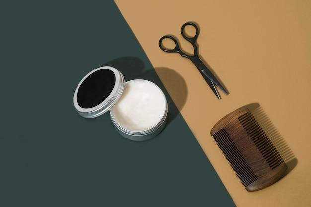 Friseurausrüstung mit kamm, schere und wachs auf grünem und braunem hintergrund