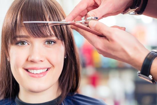 Friseurausschnittfrau schlägt haar im shop