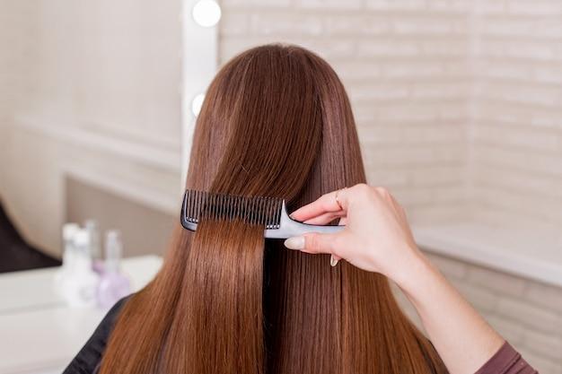 Friseure, die langes brünettes haar im schönheitssalon bürsten