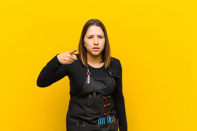 Friseurfrau, die auf kamera mit einem verärgerten aggressiven ausdruck aussieht wie ein wütender verrückter chef zeigt